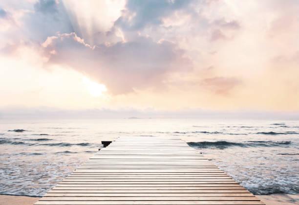 아름 다운 하늘과 햇빛 배경으로 여행 위한 도보 멀다 바다에 다리를 나무. 스톡 사진