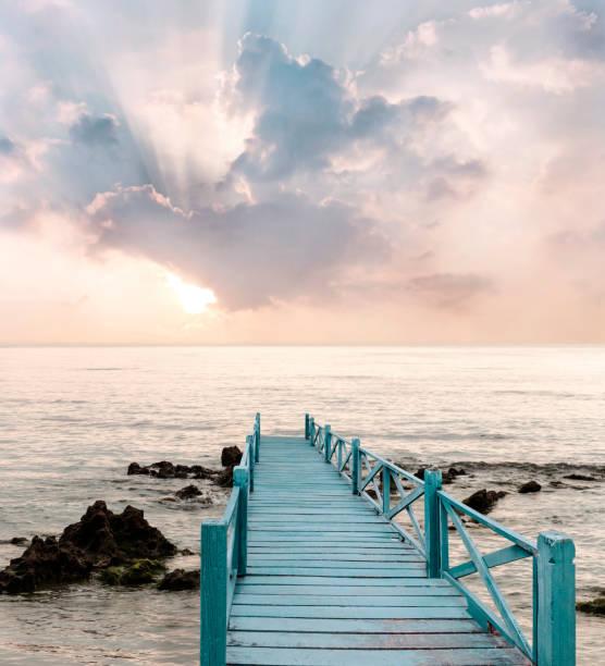 아름다운 하늘과 햇빛 배경으로 여행을위한 길을 가지고있는 바다에 나무 다리. 스톡 사진