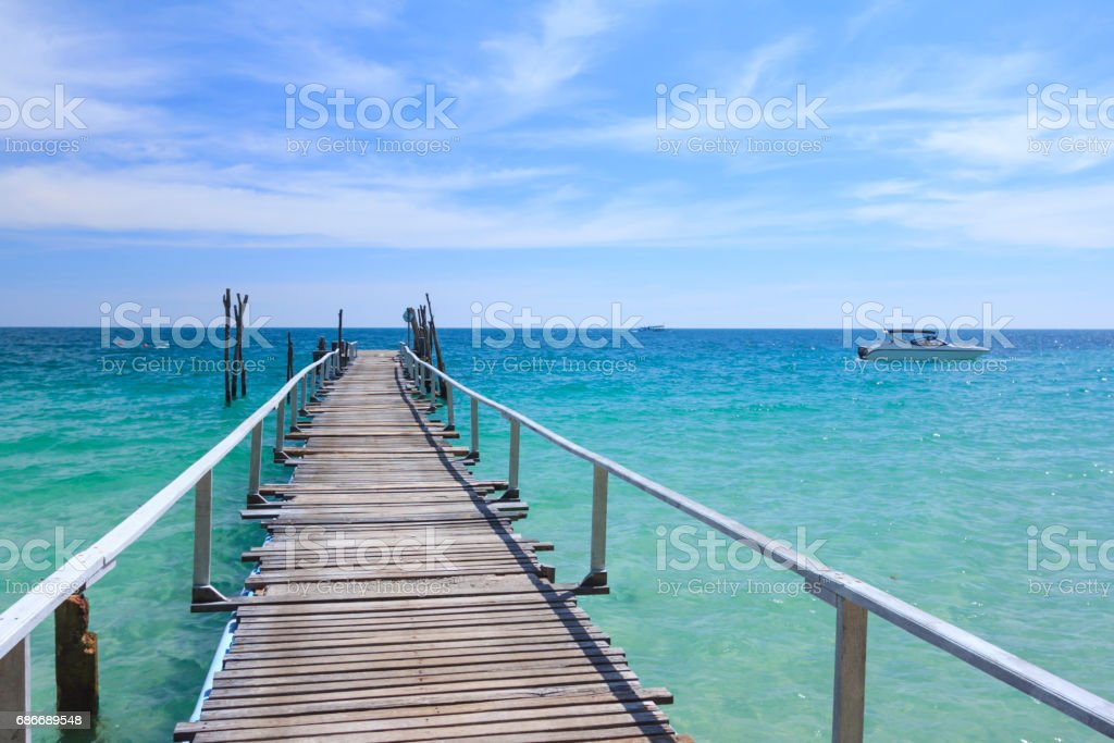 Wood bridge pier on summer tropical sea in blue sky. stock photo
