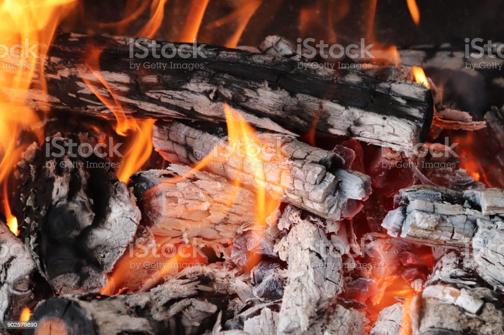 Wood burning in a fire which will eventually turn into coals which will be used to braai (cook) meat. stock photo