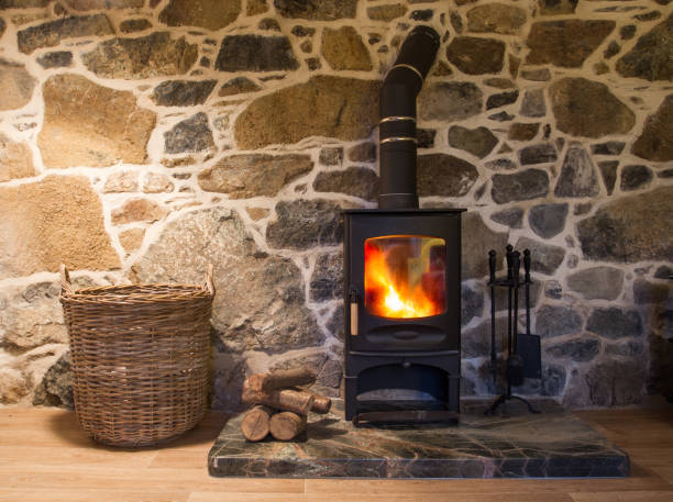 Wood Burning Stove And Fireplace The interior of a stone walled cottage with a blazing wood burner or log burning stove on a hearth with logs and storage basket. log fire stock pictures, royalty-free photos & images