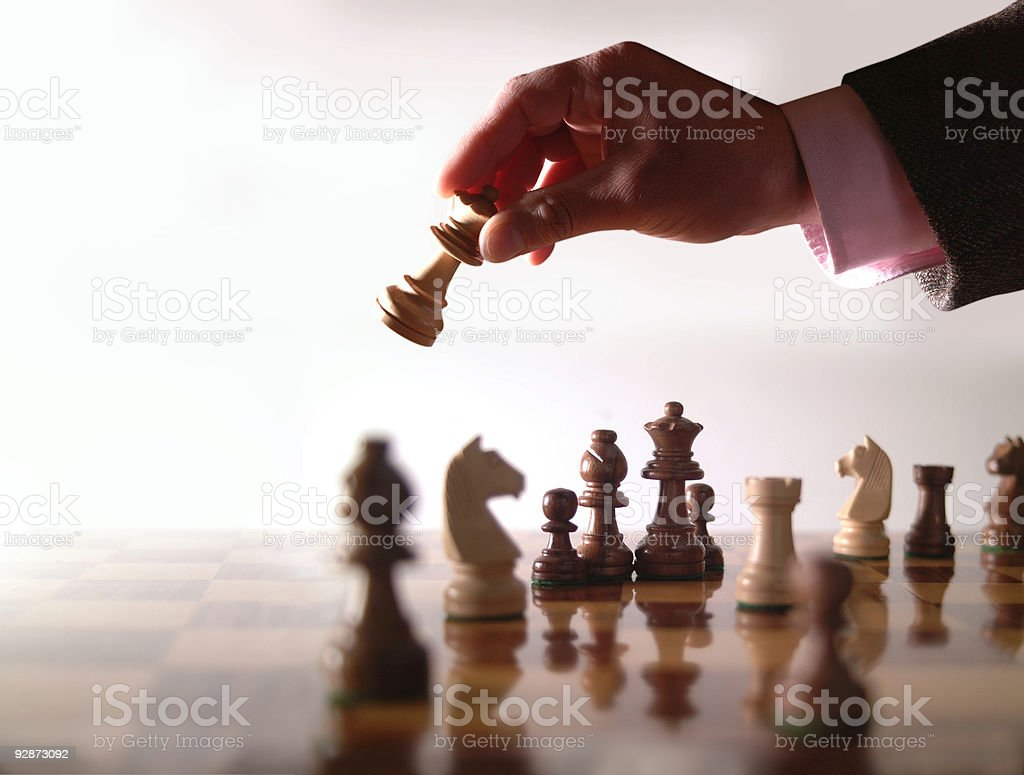 Wood chess board and hand holding queen stock photo