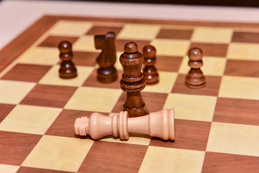 wood chess pieces on board game. brown vintage background. checkmate. the king is defeated by the queen.