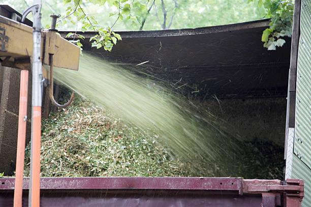 wood chipper spewing chips in kipper - häcksler stock-fotos und bilder