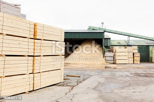 istock Wood chips and stacked wooden planks for biomass fuel at sawmill 1038437176
