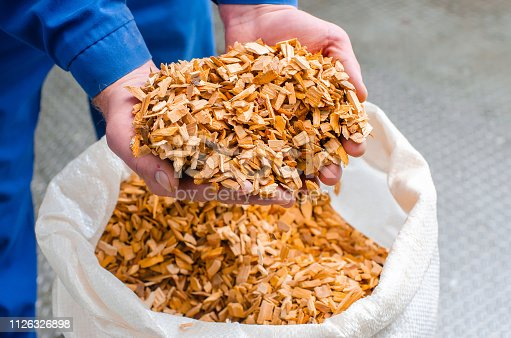 Wood chips. The line for the production of smoked delicacies. Industrial manufacture of sausage products. Smokehouse of meat products.
