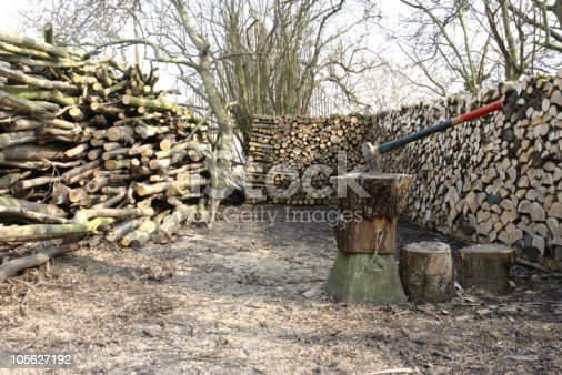 Stacked wood with an axe on a chop block in the foreground.