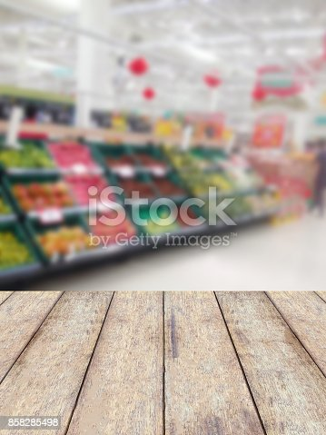 1072974214 istock photo wood counter product display with fruits shelves in supermarket blurred background 858285498