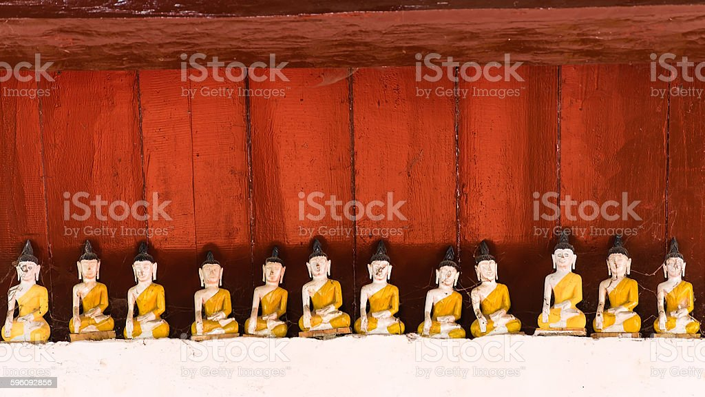 wood crafted yellow buddha image with red wooden background royalty-free stock photo