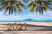 istock Wood cube number 2021 on planks on tropical beach background 1200124256