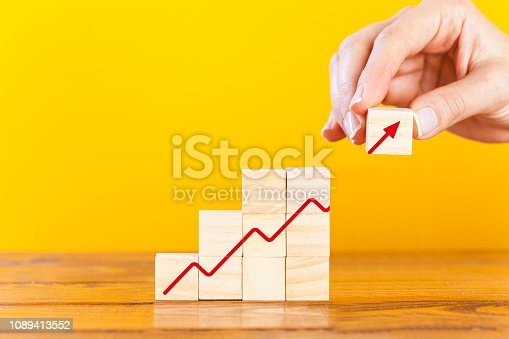 Growing graph on wooden cubes with hand putting last cube with arrow symbol. Financial growth concept