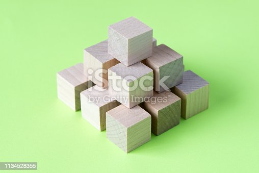 1134528355 istock photo Wood cubes arranged in pattern geometric 1134528355