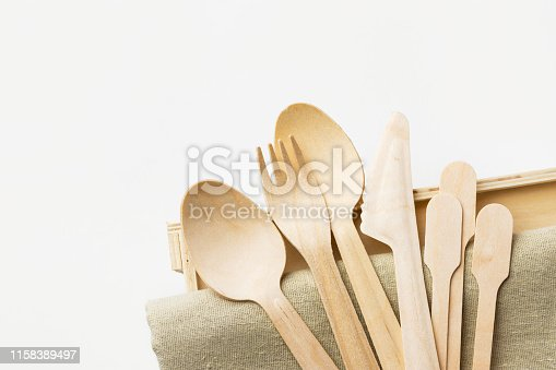 Wood cutlery spoons fork knife on beige linen cloth white wall background. Zero waste plastic free reusable biodegradable eco friendly materials. Sustainability concept. Poster