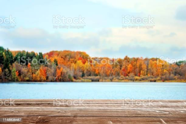 Photo of wood deck overlooking fall colored landscape and lake