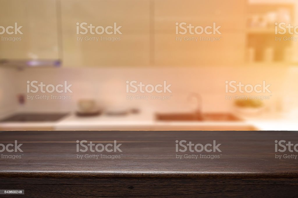 Wood desk space and blurred of kitchen background. – zdjęcie