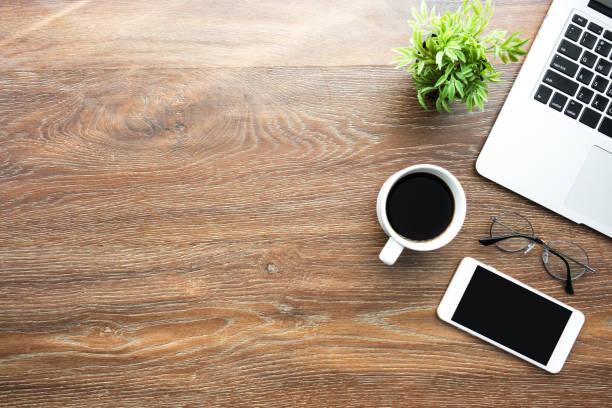 空のモックアップ画面、ノートパソコンと朝の太陽光とコーヒーのアップとスマートフォンと木製の机のテーブル。コピースペース付きトップビュー、フラットレイ。 - 机 ストックフォトと画像