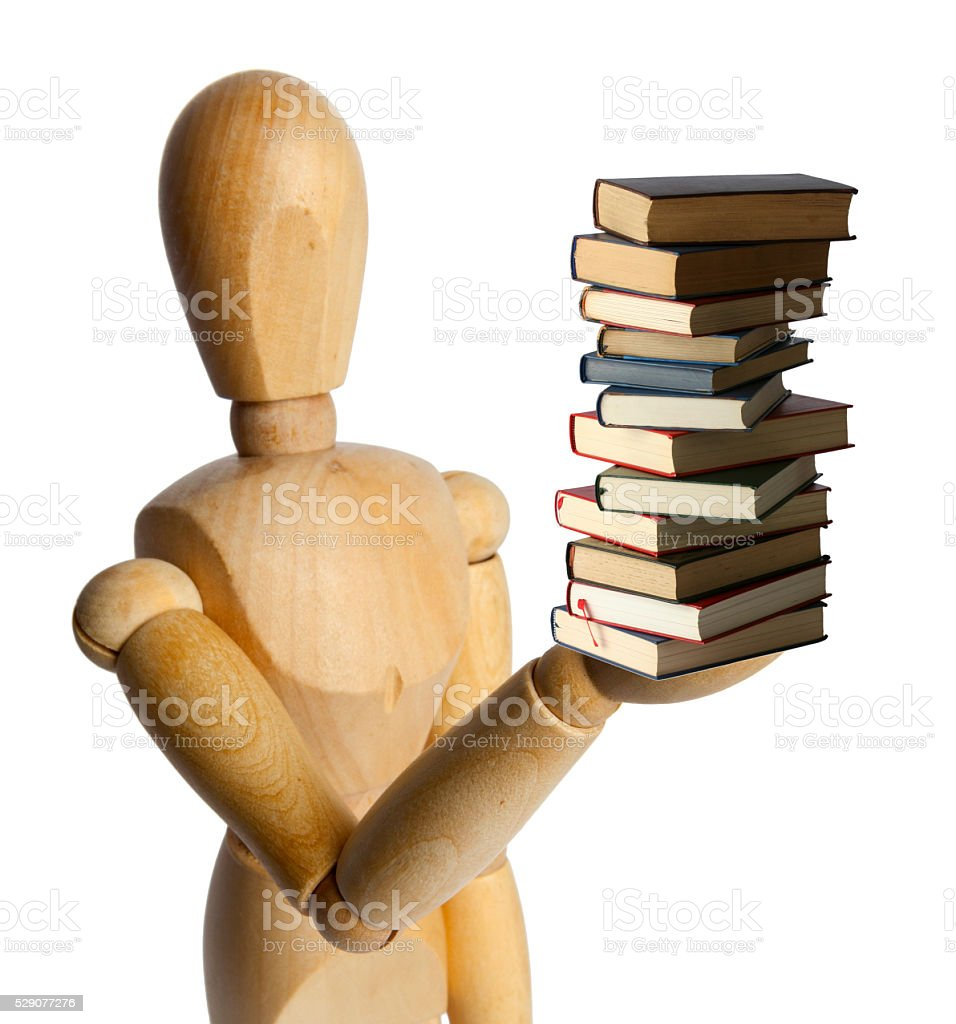 Wood Doll with a Pile of Books stock photo