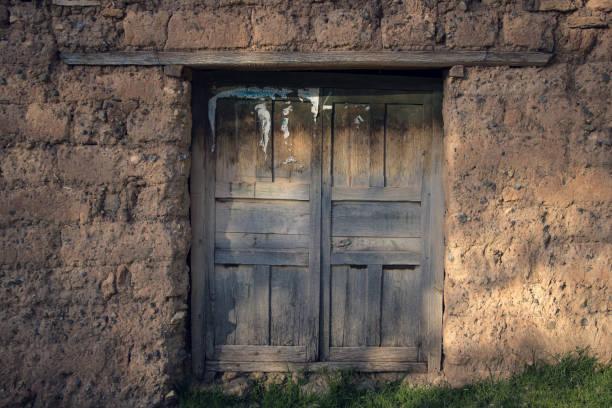 wood door in adobe house stock photo