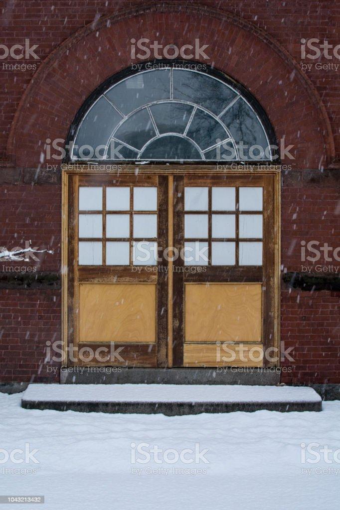 Puertas de madera en el edificio de ladrillo en nieve - foto de stock