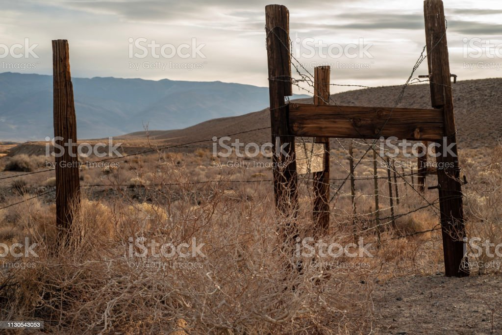 wood fence posts and barbed wire fence in mountain valley autumn...
