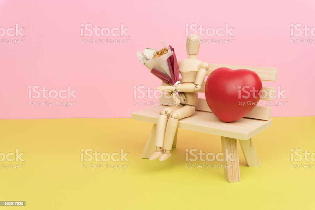 wood figure holding a bouquet of dried flower and sitting on the wooden bench - Стоковые фото Без людей роялти-фри