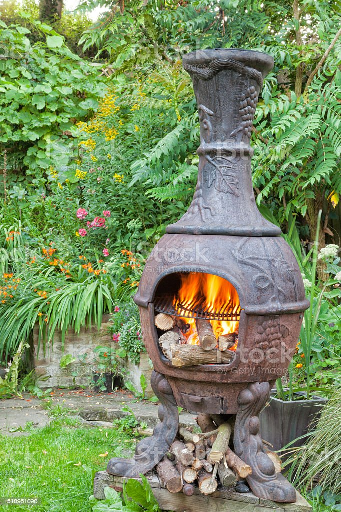 Wood fire flames in iron chiminea for garden barbecue stock photo