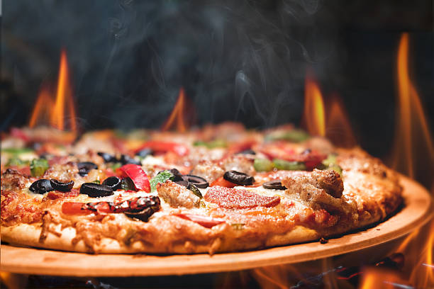 wood fired pizza with flames - italienisches essen stock-fotos und bilder