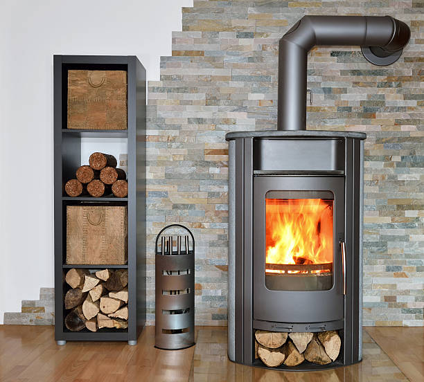 wood fired stove while burning wood fired stove with fire-wood, fire-irons, and briquettes from bark log fire stock pictures, royalty-free photos & images