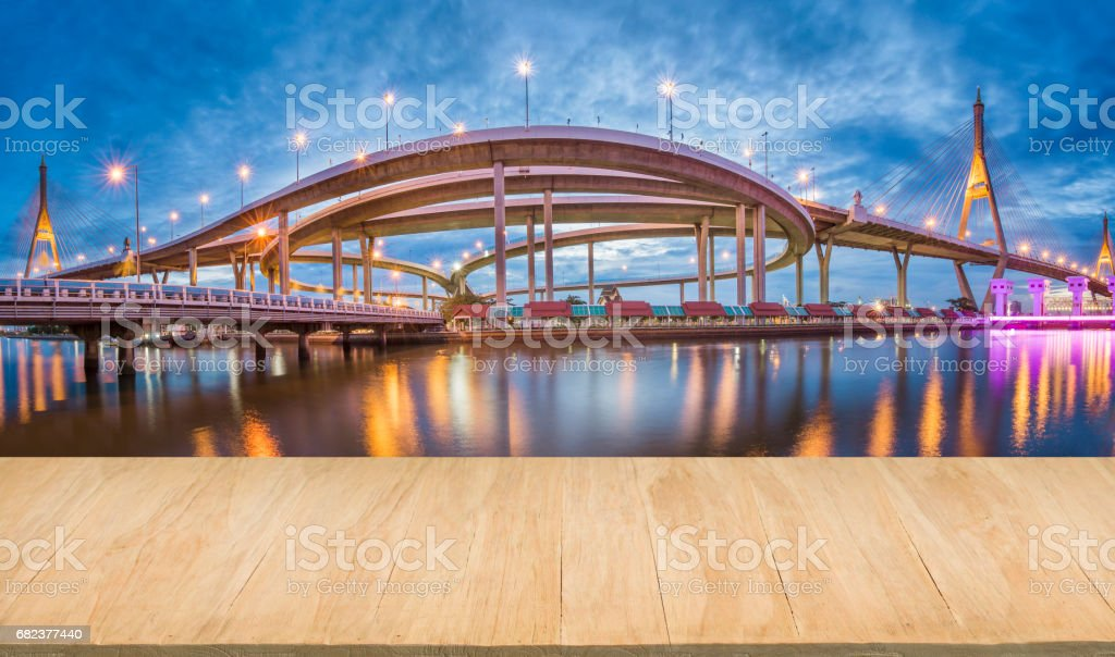 Wood floor with background of downtown and bridge at evening royalty free stockfoto