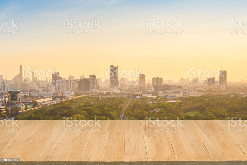Wood floor with background of downtown city at evening foto stock royalty-free