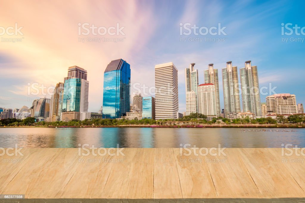 Wood floor with background of downtown city at evening zbiór zdjęć royalty-free