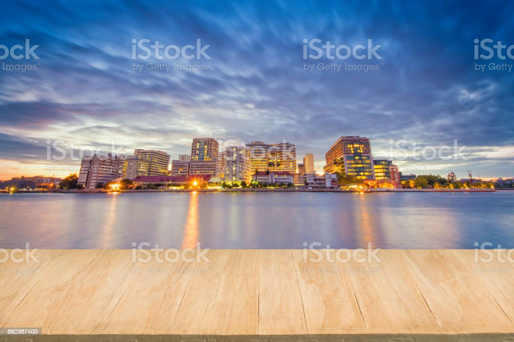 Wood floor with background of downtown city at night royalty free stockfoto