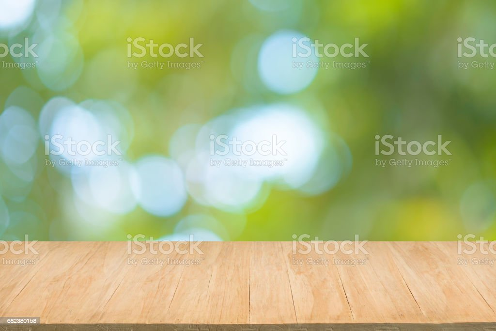 Wood floor with blur of green leaves bokeh background zbiór zdjęć royalty-free