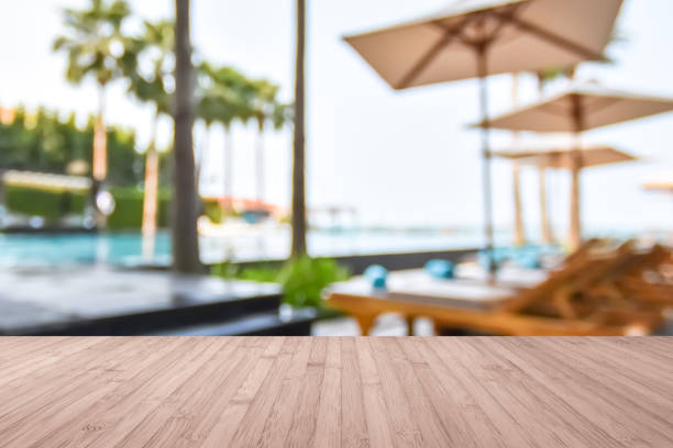 Wood floor with blur summer background tropical resort hotel with blue swimming pool and palm tree Wood floor with blur summer background tropical resort hotel with blue swimming pool and palm tree poolside stock pictures, royalty-free photos & images