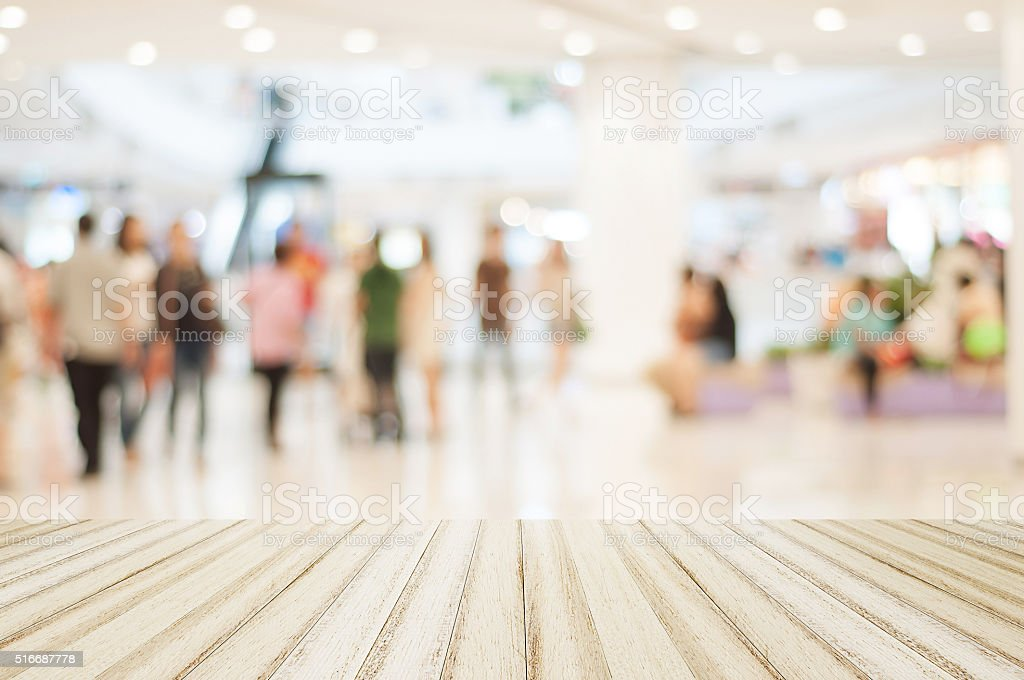 Wood floor with blurred people in shopping mall for background stock photo