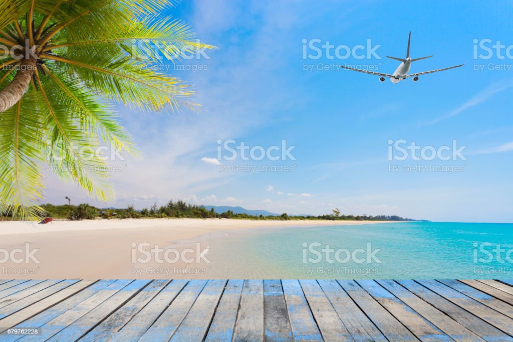 Wood floor with coconut palm trees on tropical island and airplane,concept summer and travel background. stock photo