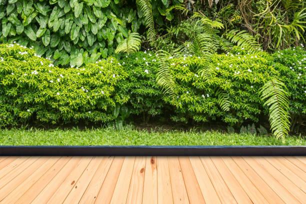holzboden in einem dekorativen grünpflanze-garten - naturholzmöbel stock-fotos und bilder