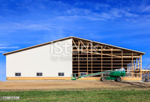 Small commercial building under construction with cherry picker in the foreground and blue sky in the background.