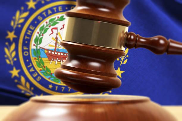 O Gavel de madeira que está a frente do close up 3D da bandeira de New Hampshire rende - foto de acervo
