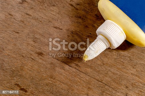istock Wood glue with blank blue label on a wooden surface 827164112