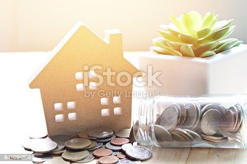 istock Wood house model and coins scattered from glass jar on wooden background 841094890