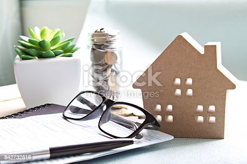 istock Wood house model, coins, eyeglasses and saving account book or financial statement on office desk table 842732516