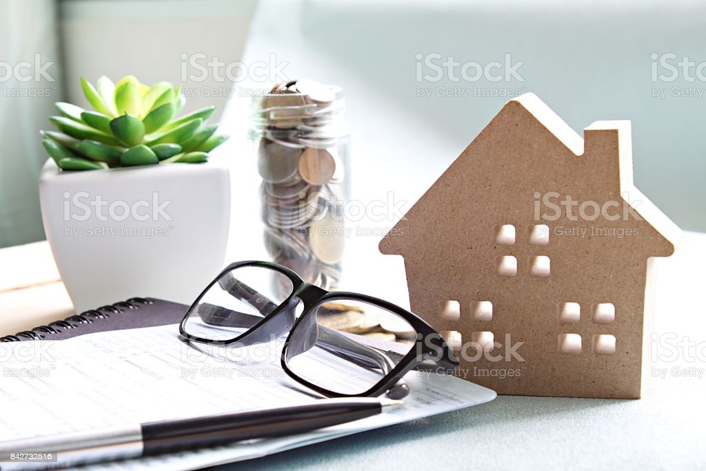 Wood house model, coins, eyeglasses and saving account book or financial statement on office desk table stock photo