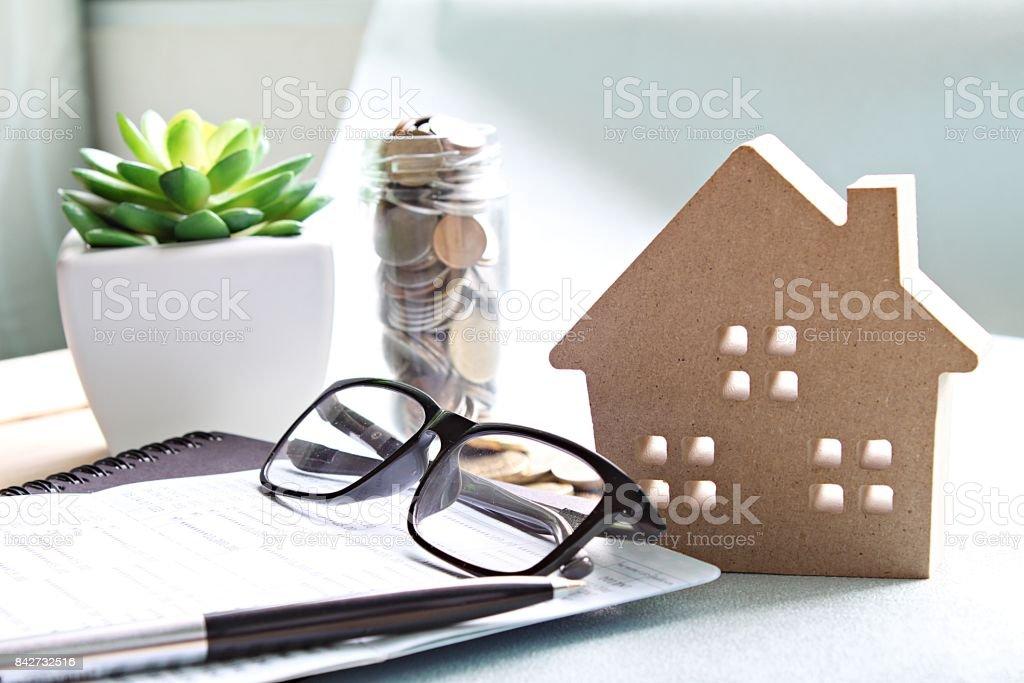 Libro de casa de madera modelo, monedas, gafas y ahorro de cuentas o Estados financieros en mesa de escritorio de oficina - foto de stock