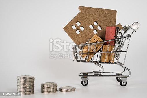 1164727388 istock photo Wood house model in shopping cart and row of coin money on white background. Real Estate market, Trading Estate, Mortgage Concepts. 1145799733