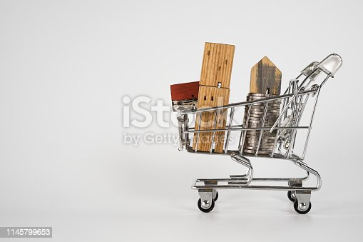 1164727388 istock photo Wood house model in shopping cart on white background. Real Estate market, Trading Estate, Mortgage Concepts. 1145799653