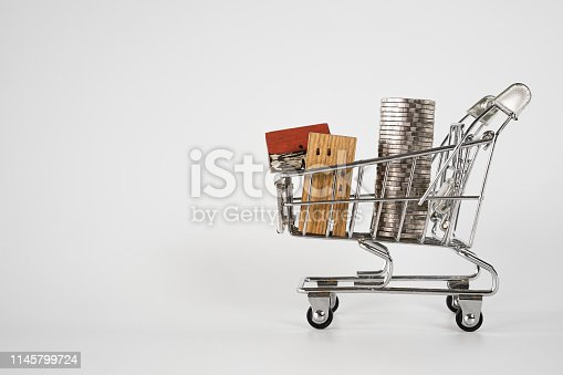 1164727388 istock photo Wood house model in shopping cart on white background. Real Estate market, Trading Estate, Mortgage Concepts. 1145799724