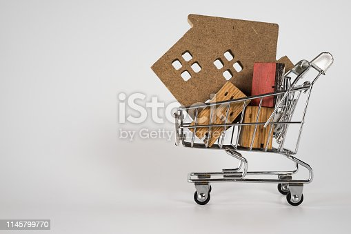 1164727388 istock photo Wood house model in shopping cart on white background. Real Estate market, Trading Estate, Mortgage Concepts. 1145799770
