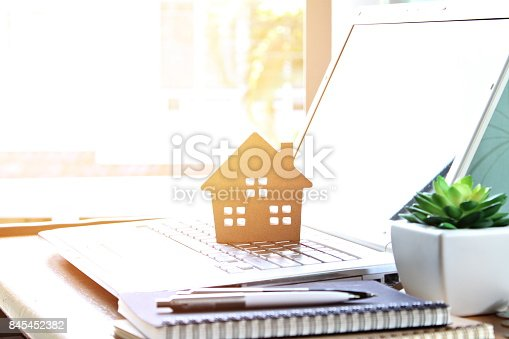 istock Wood house model on computer laptop 845452382