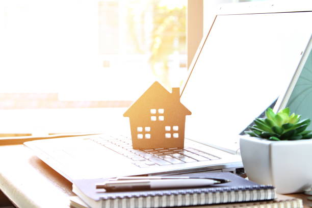 Wood house model on computer laptop stock photo